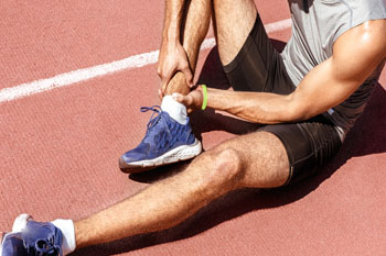 Man holding onto sore ankle - sports medicine
